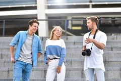 Group of happy friends chatting in the street. Friendship concept. stock image
