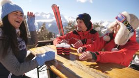 Smiling friends spending time together and drink after skiing in cafe at ski resort in mountains. Group of happy friends cheering with drink after skiing day in stock video footage