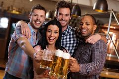Group of happy friends clinking with beer in pub. Group of happy young friends drinking beer at pub, laughing, clinking glasses Stock Images