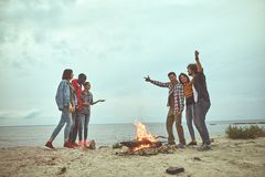 Group of happy friends are dancing on seaside. Get together. Happy friends standing near bonfire while telling stories each other at the sea shore royalty free stock photography