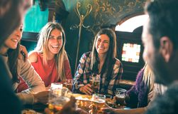 Group of happy friends drinking beer at brewery bar restaurant. Friendship concept with young millenial people enjoying time together having fun vintage pub stock image