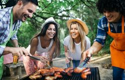 Group of happy friends eating and drinking beers at barbecue dinner royalty free stock photos