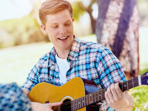Group of happy friends with guitar having fun outdoor Stock Photography