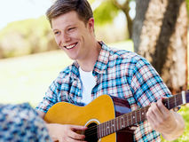 Group of happy friends with guitar having fun outdoor Stock Images