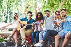 Group of happy friends with guitar. While one of them is playing guitar and others are giving him a round of applause royalty free stock photography
