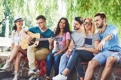 Group of happy friends with guitar. While one of them is playing guitar and others are giving him a round of applause Royalty Free Stock Photos