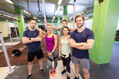 Group of happy friends in gym. Fitness, sport and people concept - group of happy friends in gym royalty free stock image