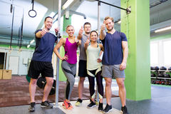 Group of happy friends in gym. Fitness, sport and people concept - group of happy friends in gym showing thumbs up gesture Stock Image