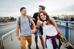Group of happy friends hang out together. Carrying skateboards royalty free stock photography