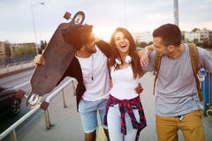 Group of happy friends hang out together. Carrying skateboards Stock Images