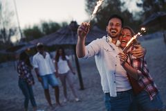 Group of happy friends having fun on beach at night. Playing with sparklers Stock Photo