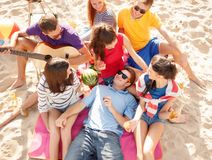 Group of happy friends having fun on beach. Summer holidays, vacation, music, happy people concept - group of happy friends having picnic and playing guitar on royalty free stock images