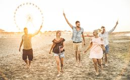 Group of happy friends having fun on the beach at sunset Stock Images