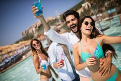 Group of happy friends having fun dancing at swimming pool outdoors. Group of happy friends having fun dancing at swimming pool with cocktails royalty free stock photo