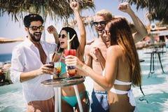 Group of happy friends having fun dancing at swimming pool outdoors. Group of happy friends having fun dancing at swimming pool with cocktails stock photos