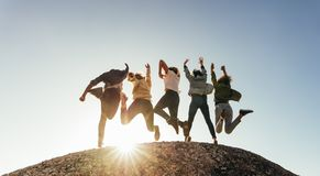 Group of happy friends having fun on mountain top. Rear view of group of happy friends having fun on mountain top. Men and women jumping on mountain top against