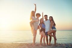 Group of happy friends having fun at ocean beach at dawn stock image