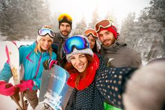 Group of happy friends having fun Snowboarders and skiers making. Group of happy friends having fun on the snow. Snowboarders and skiers making selfie Royalty Free Stock Photo