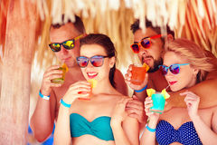 Group of happy friends having fun on tropical beach, drinking colorful cocktails Royalty Free Stock Photo