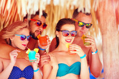 Group of happy friends having fun on tropical beach, drinking colorful cocktails Stock Photography