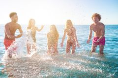 Group of happy friends having fun with water sea at ocean beach at dawn royalty free stock photos