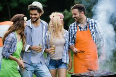Group of happy friends having outdoor barbecue laughing together stock image