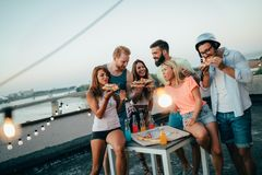 Group of happy friends having party on rooftop stock images