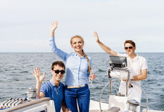 Group of happy friends having a party on a yacht and drinking ch Stock Image