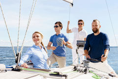 Group of happy friends having a party on a yacht and drinking ch Stock Photography
