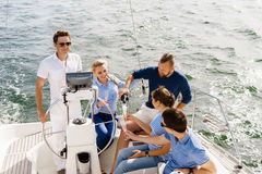 Group of happy friends having a party on a yacht. And drinking champagne. Vacation, holiday, traveling, concept stock photos