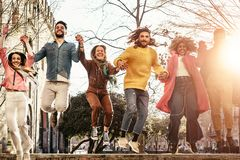Group of happy friends jumping outdoor - Millennial young people having fun dancing and celebrating at sunset outside