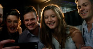 Group of happy friends looking at mobile phone. In bar 4k stock video
