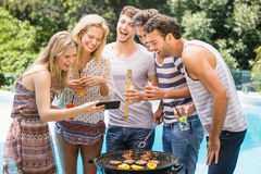 Group of happy friends looking at mobile phone Royalty Free Stock Images