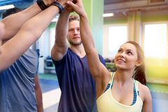 Group of happy friends making high five in gym. Fitness, sport, exercising, gesture and people concept - group of happy friends making high five in gym royalty free stock image