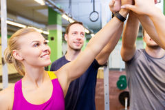 Group of happy friends making high five in gym Stock Photo