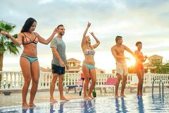 Group of happy friends making a pool party at sunset - Young people having fun dancing next to the pool stock images