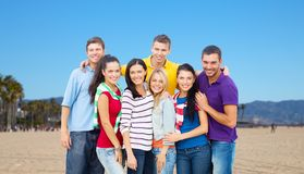 Group of happy friends over venice beach. Travel, tourism and people concept - group of happy friends pointing over venice beach background in california stock image