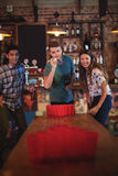 Group of happy friends playing beer pong game. In pub Royalty Free Stock Image