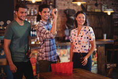 Group of happy friends playing beer pong game. In pub Royalty Free Stock Photos