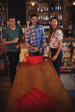 Group of happy friends playing beer pong game. In pub Stock Photography