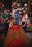 Group of happy friends playing beer pong game. In pub Stock Photo