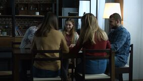 Group of happy friends playing board game at table. Group of cheerful teenage friends having fun and playing board game while sitting at the table in domestic stock video