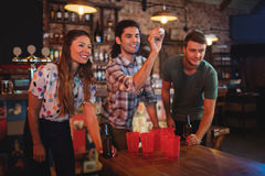 Group of happy friends playing game. In pub Royalty Free Stock Image
