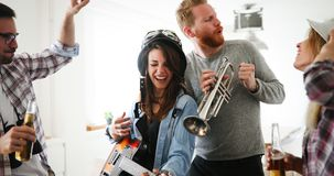 Group of friends playing guitar and partying at home. Group of happy friends playing guitar and partying at home Royalty Free Stock Image