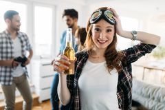 Group of friends playing guitar and partying at home. Group of happy friends playing guitar and partying at home Stock Image