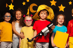 Group of happy friends playing sky watchers. Group of happy friends standing in a row, playing sky watchers with telescope, against starry night sky stock photos
