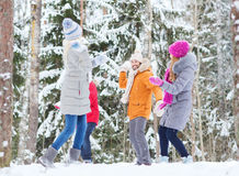 Group of happy friends playing snowballs in forest Royalty Free Stock Image