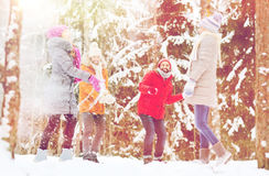 Group of happy friends playing snowballs in forest Stock Images
