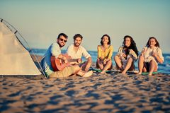 Happy friends relaxing with playing guitar and sing a song toget. Group of happy friends relaxing with playing guitar and sing a song together on sea beach stock images