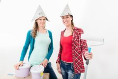 Group of happy friends renovating new house. Portrait of happy friends wearing newspaper hat renovating new house stock images